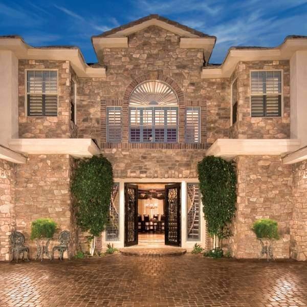 Отделка фасада двухэтажного дома искусственным камнем